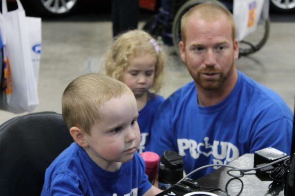 A young boy in a wheelchair and his father and sister play a videogame