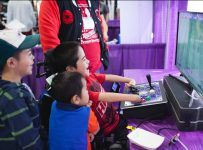 Kids gathered around specialized game controlled laughing and playing video games